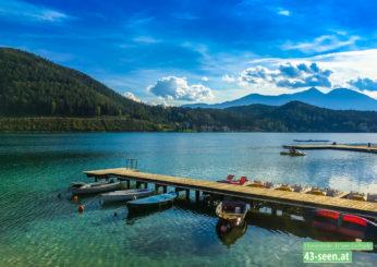 Steg mit angelegten Booten und Tretboot im Hintergrund